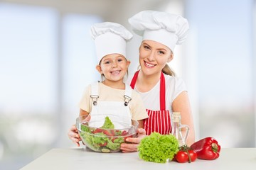 Attractive. Cute young girl cooking with her parents in the