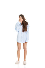 Young yawning woman in big shirt.