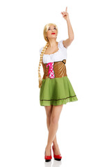 Woman in Bavarian dress pointing up.