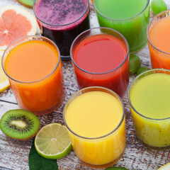 Glasses of tasty fresh juice, on wooden desk.