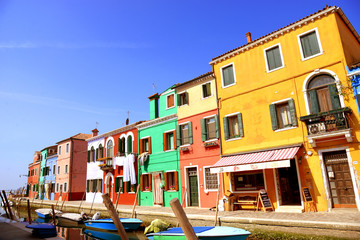 Burano island canal, colorful houses and boats, Italy