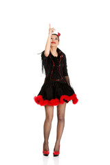 Woman in devil carnival costume pointing up.
