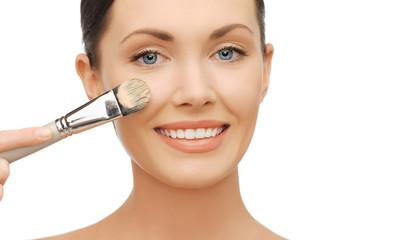 woman applying liquid foundation with brush