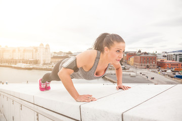 Young woman doing push-ups exercises