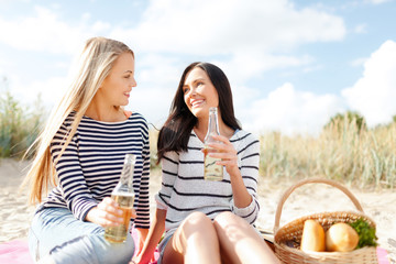 happy young women drinking beer on beach