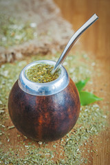 Latin traditional yerba mate tea in calabash with bombilla on