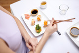 close up of woman eating sushi at restaurant