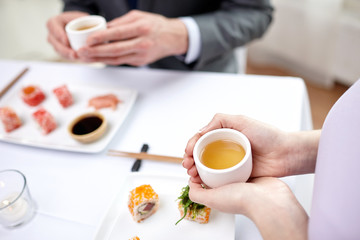 close up of couple drinking tea at restaurant