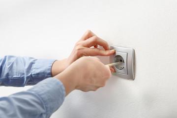 Electrician installing AC power socket