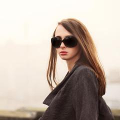 portrait of a beautiful brunette wearing sunglasses in winter