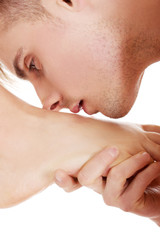 Young man kissing woman's bare feet.