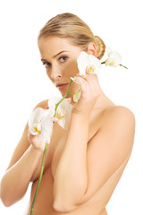Spa woman holding white orchid flower