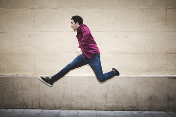 Real man jumping with clear background wall