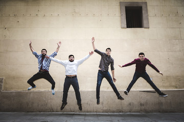 Group of friends jumping with clear background wall