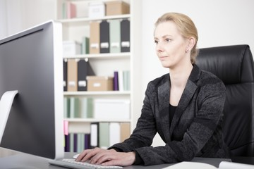 Serious Businesswoman at Desk Typing on Computer