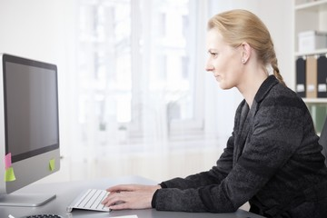 Happy Businesswoman in Side View Tying on Computer