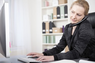 Businesswoman Talking on Phone Typing on Computer