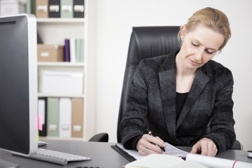 Adult Businesswoman Writing on Top of her Desk