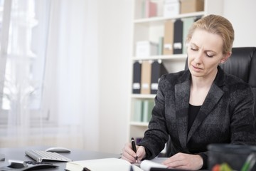 Adult Businesswoman at her Desk Writing on Paper