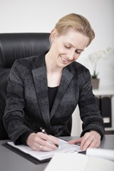 Sitting Happy Businesswoman Writing at her Desk