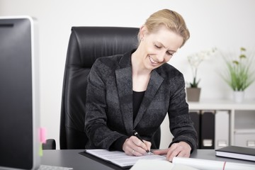 Happy Office Woman Writing a Document at her Table