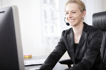 Happy Woman Customer Support Facing at her Monitor