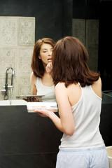 Woman applying lipstick.