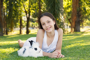 Cute beautiful smiling teen girl with white and black baby rabbi