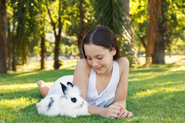 Cute beautiful smiling teen girl looking at white-black rabbit