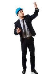 Businessman in hard hat showing copyspace.