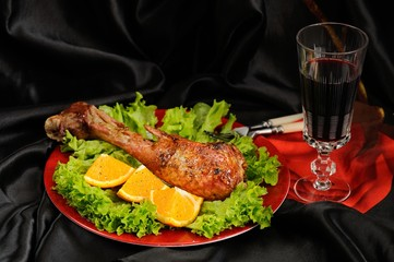 Roasted turkey drumstick with orange, lettuce and red wine on bl