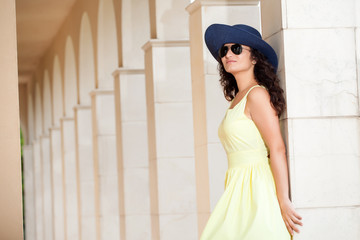 young woman with hat, sunglasses and yellow dress