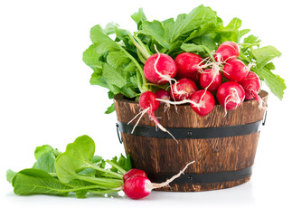Fresh radish with green leaves in wooden bucket. Isolated on