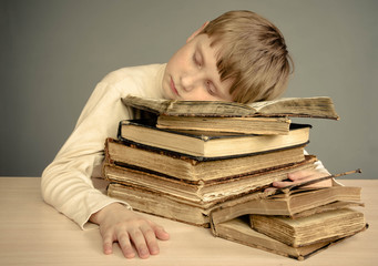 The boy asleep on a pile of old books