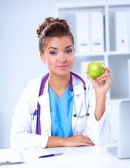 Female doctor hand holding a green apple, sitting at the desk