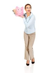 Woman holding piggy bank.