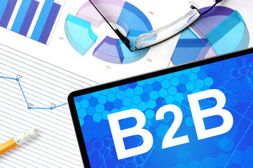 Tablet with b2b  Business to Business, graphs and glasses.