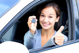 Fototapety Happy girl in a car showing a key and thumb up gesture