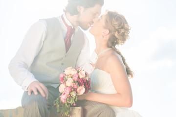 Hochzeitspaar bei Hochzeit küsst auf Feld