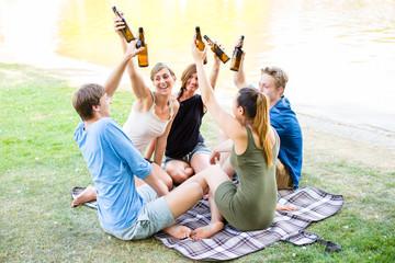 Freunde sitzen in Runde trinken Bier am See