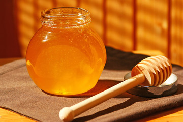 Glass jar with honey and wood stick