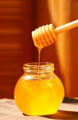 Jar of honey with wood stick