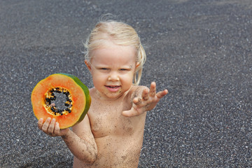 Little cute girl on the sea beach with sweet orange papaya