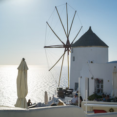 old mill and sun reflex in the sea on Santorini in Greece