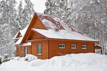 Big wooden house at the snowy winter forest