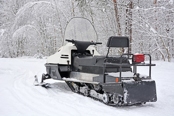 Snowmobile at the winter forest. Snowy road