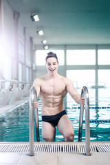 Young muscular swimmer on the ladder