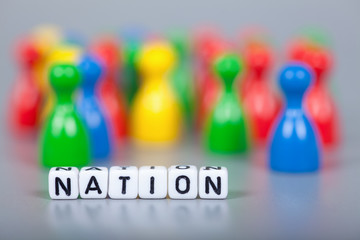 Cube Letters show nation  in front of unsharp ludo figures