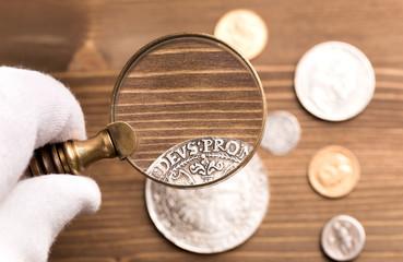 Examining old silver coin