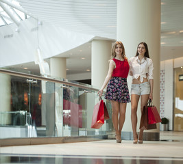 Two girlfriends on shopping walk on shopping centre with bags